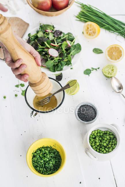 Blick auf Händen bereitet Salat, gewürzt mit Pfeffer beschnitten — Stockfoto
