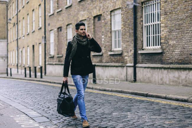Joven hombre de negocios casual caminando por la calle usando el teléfono móvil - foto de stock