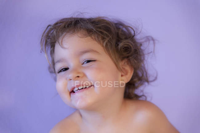 Portrait of smiling little girl in front of purple background — Stock Photo