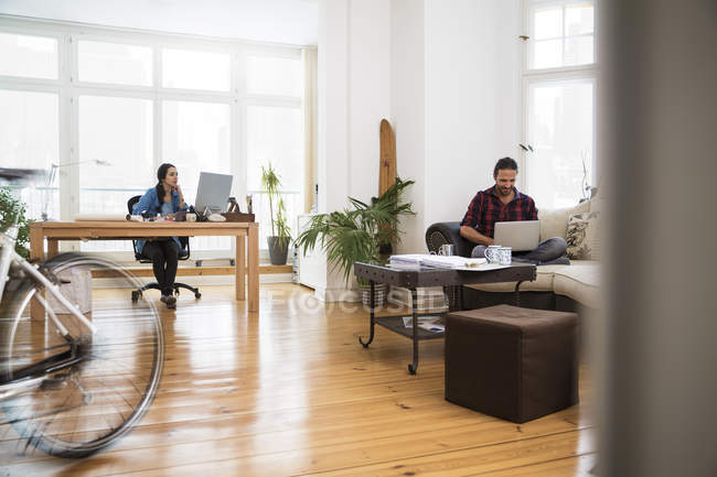 Two creative business people working in informal office — Stock Photo