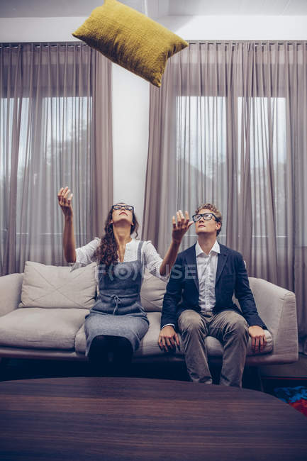 Young couple at home sitting on sofa with cushion flying mid-air — Stock Photo