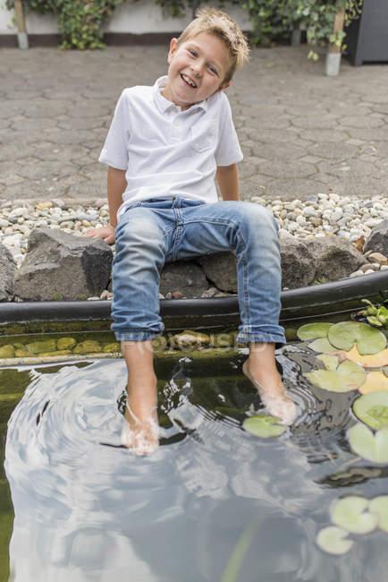 Ritratto di bambino piedi rinfrescanti in uno stagno di giglio — Foto stock