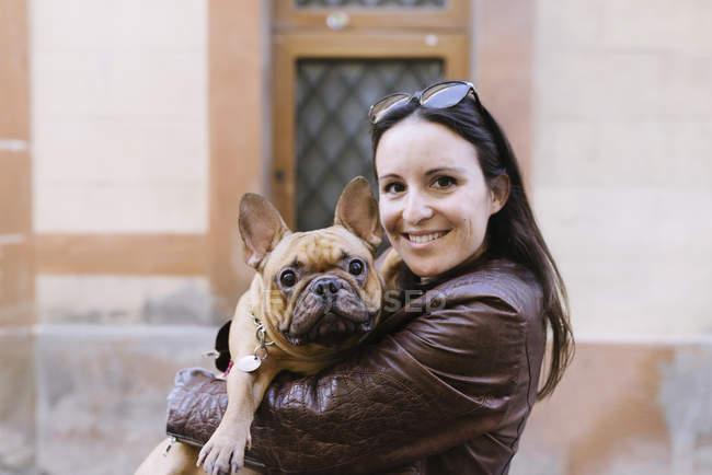 Portrait de bulldog français sur les bras d'une jeune femme souriante — Photo de stock