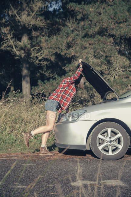 Young woman examining damaged car — Stock Photo
