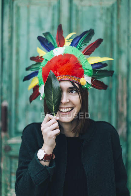 Portrait of woman wearing Indian headdress covering one eye with a leaf — Stock Photo