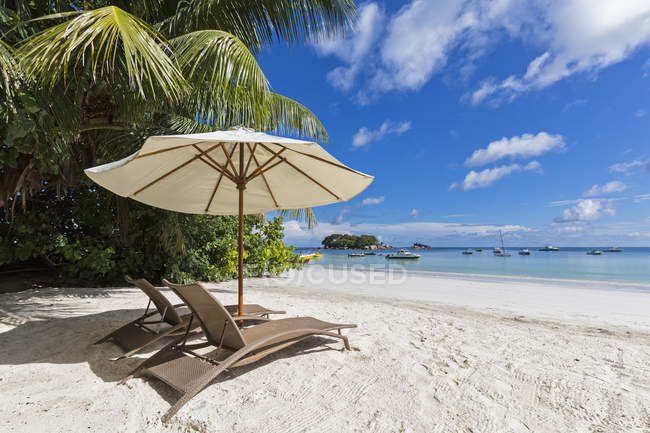 Seychelles, Praslin, Anse Volbert, Chauve Souris Island and Saint Pierre, beach with sun loungers — Stock Photo