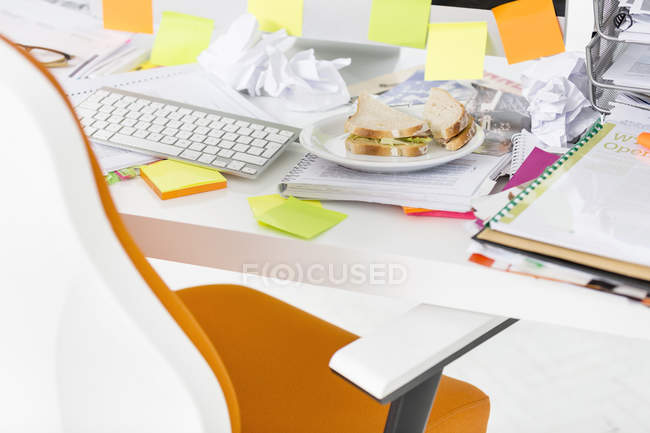 Plate with sandwiches on desk in office — Stock Photo