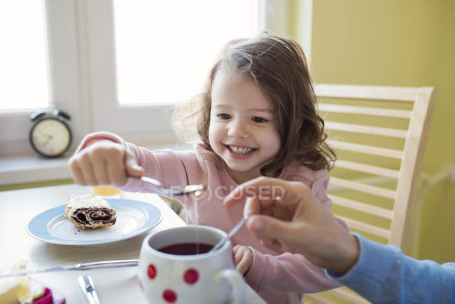 Girl putting honey at mother tea — Stock Photo
