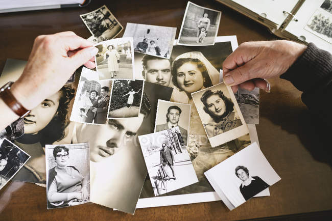 Hands of senior couple holding old photographies of themselves — Stock Photo