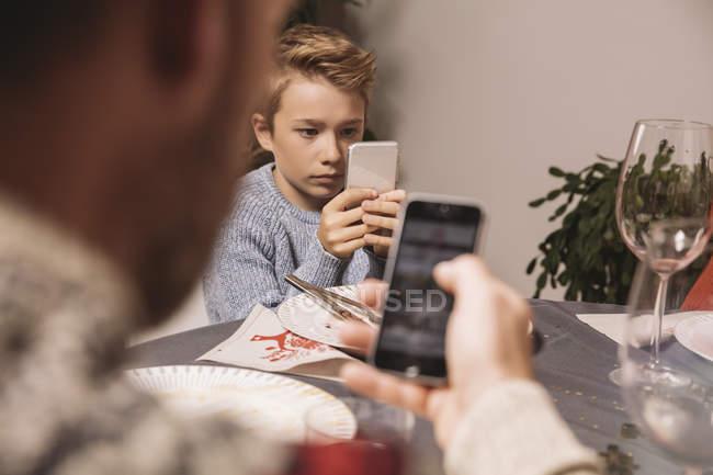 Junge und Vater spielen nach Weihnachtsessen mit Smartphones — Stockfoto