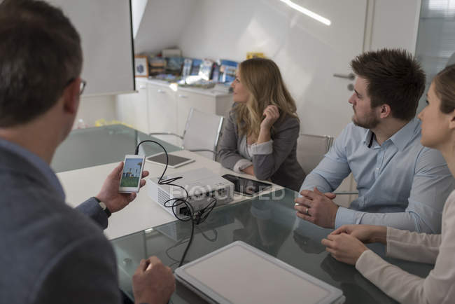 Four colleagues attending a presentation with smartphone and projector in conference room — Stock Photo