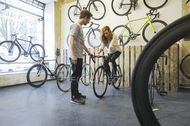 Клиент тестирует гоночный цикл в специализированном магазине велосипедов — стоковое фото