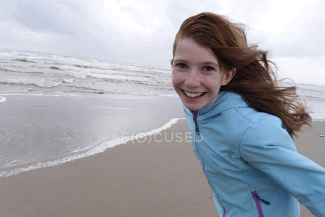 Portrait d'une rousse souriante sur un jour de grand vent sur la plage — Photo de stock