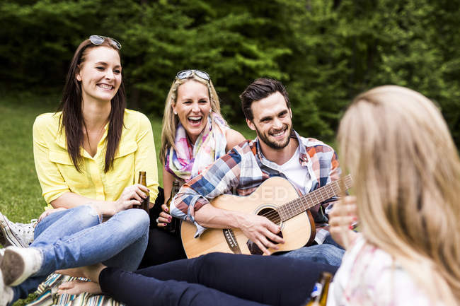Щасливі друзів гітара і пиво флакони для спокійного в парку — стокове фото