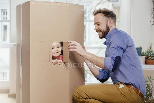 Pai de corte para fora da janela pela sua filha em casa de papelão — Fotografia de Stock