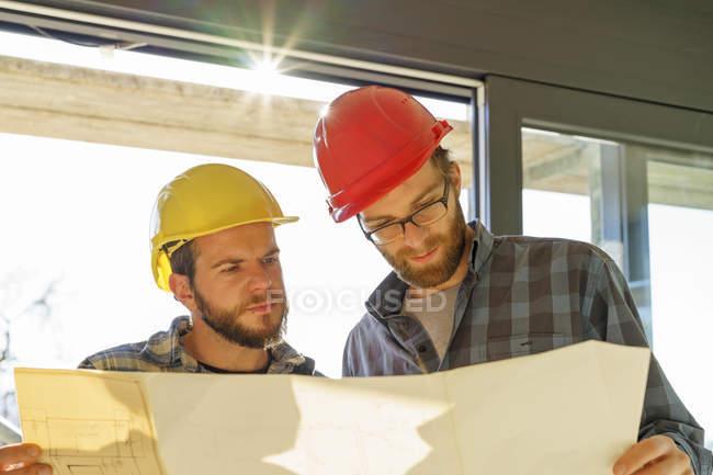 Ремісники, шукає на будівництво план — стокове фото