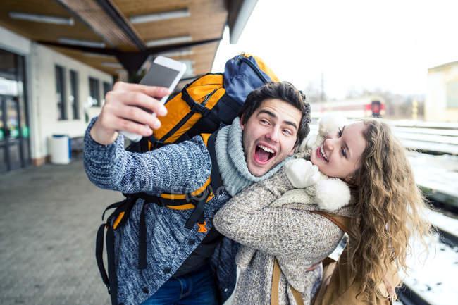 Pareja tomando selfie en estación plataforma - foto de stock