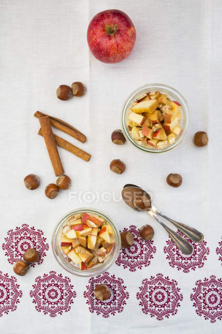 Glasses of overnight oats with sliced apple, hazelnuts and cinnamon — Stock Photo
