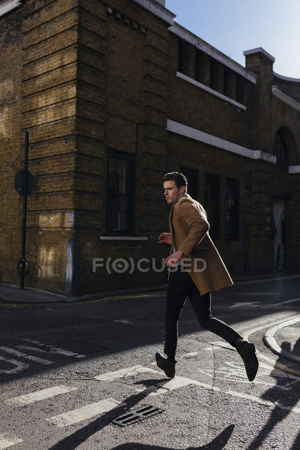 Young man in a hurry crossing urban street — Stock Photo