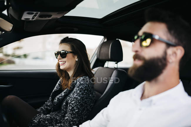 Jovem casal sorrindo dirigindo em um carro — Fotografia de Stock