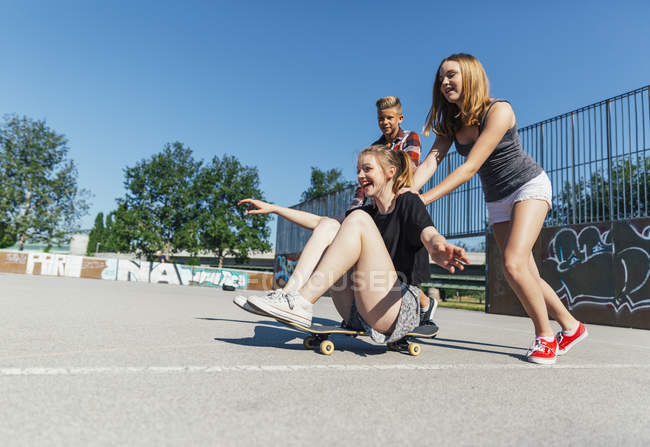 Three playful teenage friends having fun with skateboard — Stock Photo
