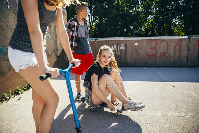 Three teenage friends having fun with scooter and skateboard — Stock Photo