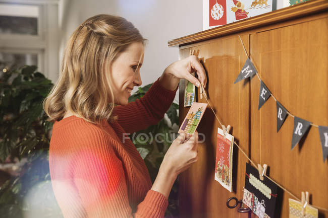 Woman hanging up Holiday cards for decoration — Stock Photo