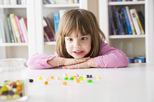 Portrait of little girl with jelly beans at table — Stock Photo