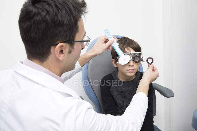 Male Optometrist examining eyesight of boy in clinic — Stock Photo