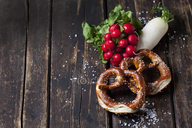 Dois biscoitos, rabanetes vermelhos, rabanete e grãos de sal dispersados em madeira escura — Fotografia de Stock