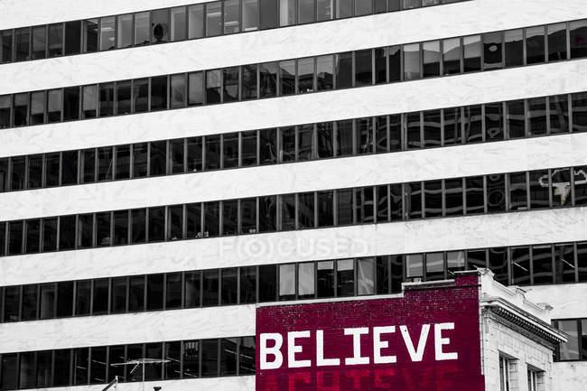 Слово верить окрашены на старый жилой дом напротив высотное здание — стоковое фото