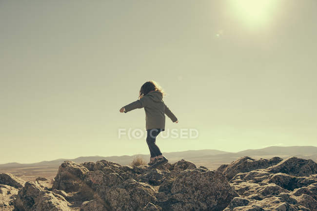 Spain, Consuegra, back view of little girl balancing on rocks in the mountains — Stock Photo
