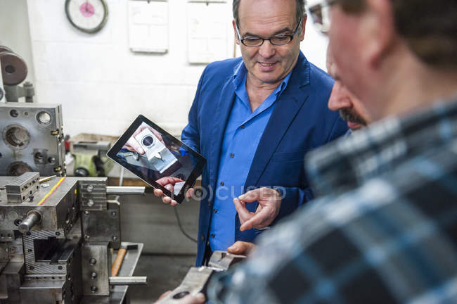 Three men with digital tablet discussing a workpiece — Stock Photo