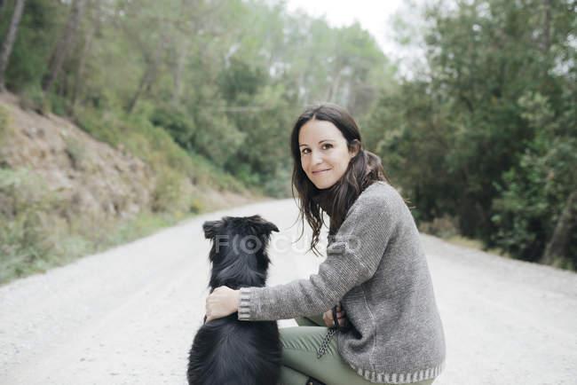 Portrait de femme souriante avec son chien dans la nature — Photo de stock