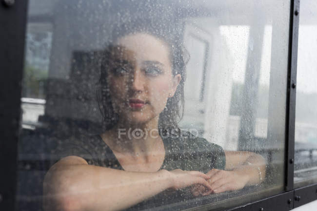 Portrait of young woman looking through window of an excursion boat on a rainy day — Stock Photo