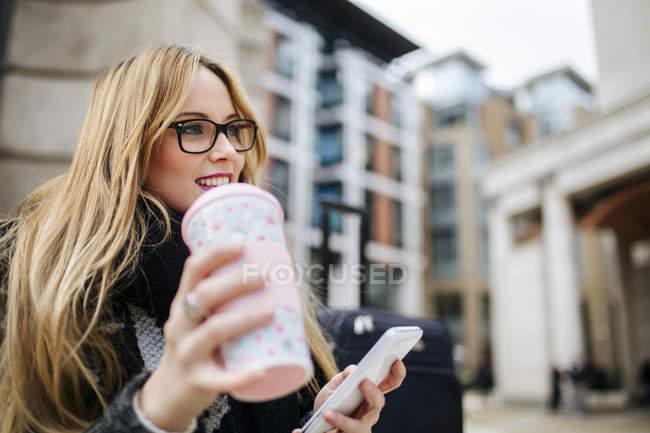 Улыбающаяся молодая женщина с кофе идти и сотовый телефон на открытом воздухе — стоковое фото