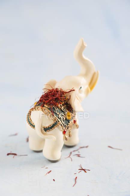 Elefant figurine and saffron threads — Stock Photo