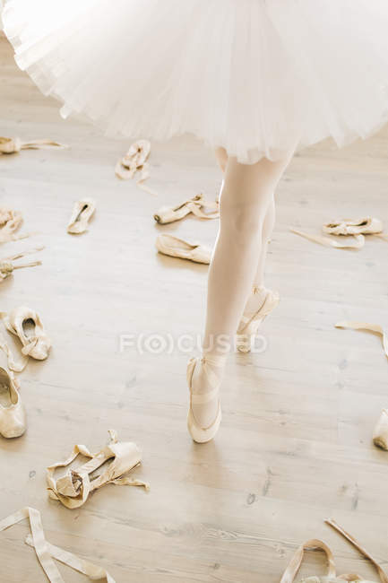 Ballerine sur pointe, vue en coupe basse, chaussures de ballet éparpillés sur le sol — Photo de stock