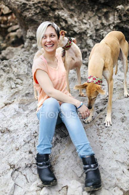 Портрет смеющейся молодой женщины со своими борзыми на пляже — стоковое фото