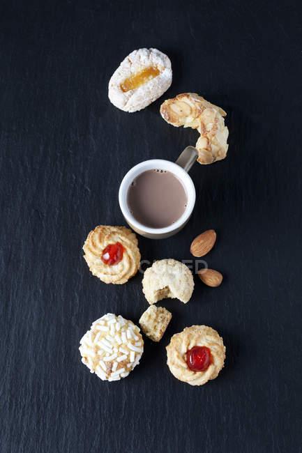 Различные виды итальянских миндальное печенье и чашку какао на шифер — стоковое фото