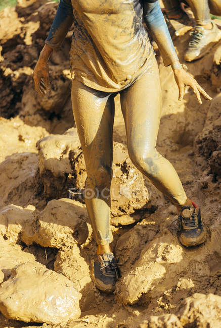 Cropped image of participants in extreme obstacle race, running through mud — Stock Photo