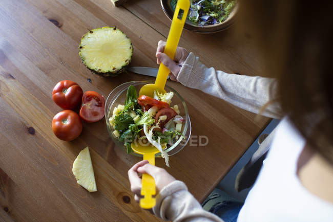 Cropped view of young woman preparing salad — Stock Photo