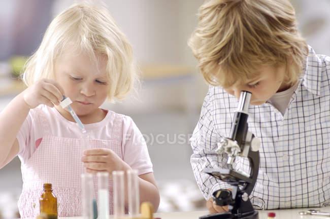 Due bambini piccoli che giocano con utensili di laboratorio chimico — Foto stock