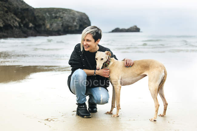 Happy young woman with her greyhound on the beach — Stock Photo
