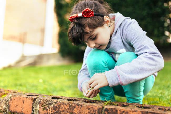 Bambina che gioca fuori con i mattoni — Foto stock