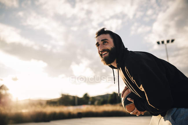 Young man playing basketball on an outdoor court — Stock Photo