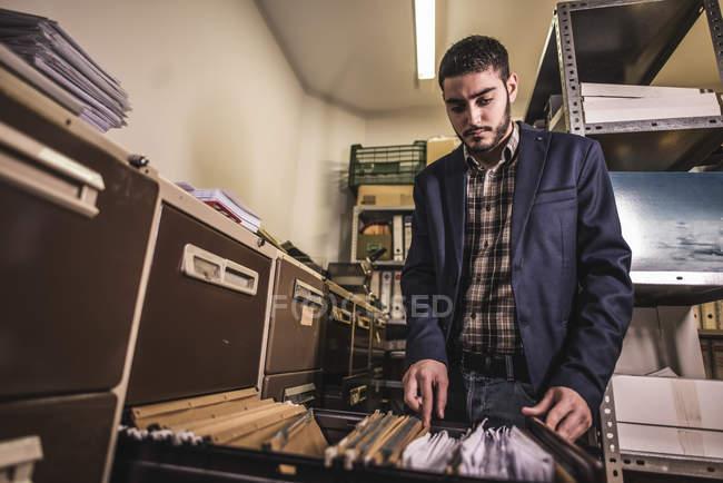 Mann auf der Suche nach Dateien im Büro Keller — Stockfoto