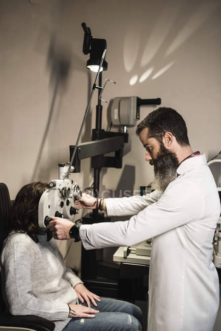 Optometrist examining woman with a phoropter — Stock Photo