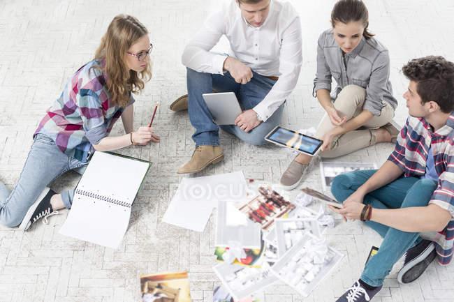 Colegas no escritório, sentada no chão com impressões fotográficas — Fotografia de Stock