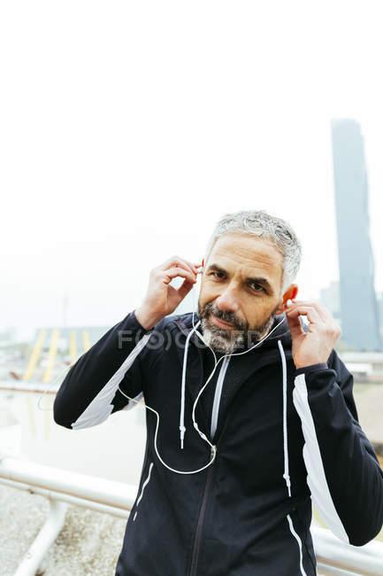 Mature athlete wearing earphones — Stock Photo